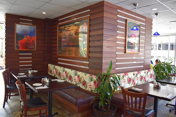 ウッドテイストの家具にハワイを感じさせるデザインのソファや観葉植物